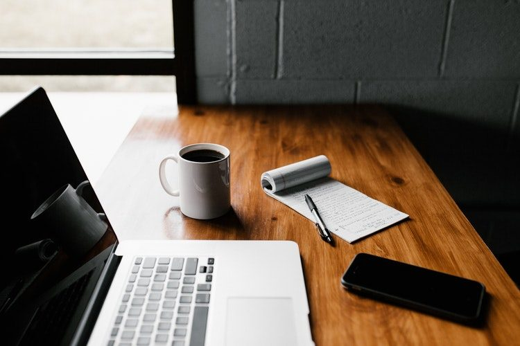 Számviteli beszámoló készítése - munkaasztal laptoppal és mobillal